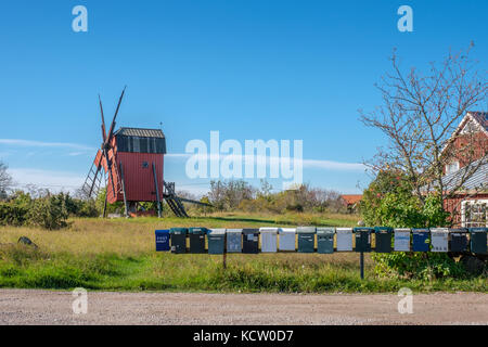 Row of mailboxes and a traditional windmill on Swedish island Oland in the Baltic Sea. Windmills are a common sight - Stock Photo