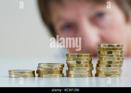 A pensioner looking concerned at a pile of British money pounds sterling new pound coins GBP in four piles. Watch - Stock Photo