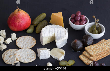 Cheese,crackers, pickles and fruit on black background close up - Stock Photo