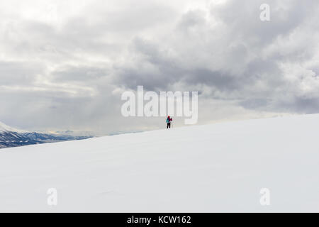 Picture is taken on a hike up Kjølen (mountain). Lonely skier in open white winter landscape. Kvaløya, Tromsø, Norway. - Stock Photo