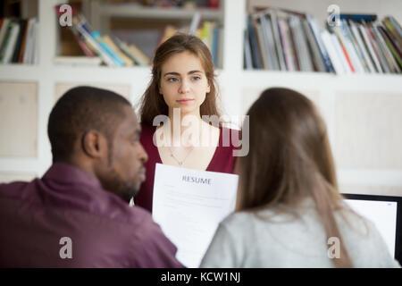 Multiethnic HR team discuss female job applicants resume. African american human resources representative listening - Stock Photo