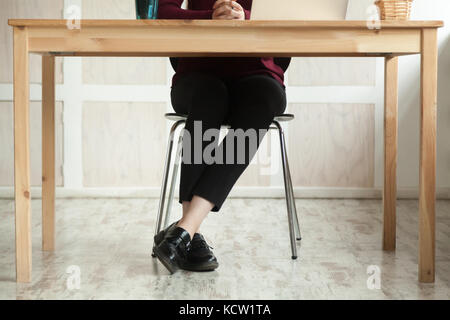 Close up legs of business lady at work desk anticipating meeting. Businesswoman preparing for briefing, having audition. - Stock Photo