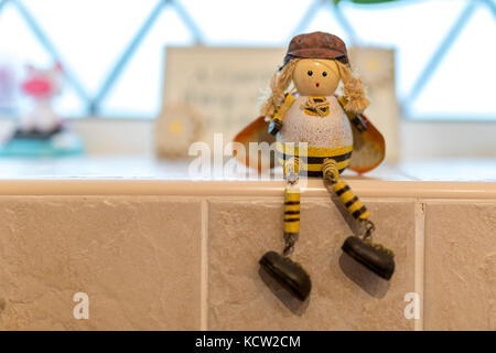 Cute tiny lady female bee artisan character ornament or toy sitting on a tiled window ledge - Stock Photo