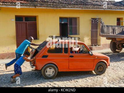 Push starting old car in Trinidad,  Cuba - Stock Photo