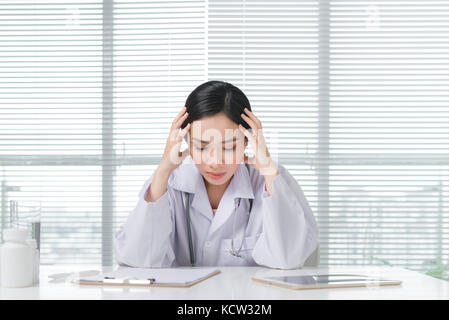 Frustration young female doctor sitting in her consulting room - Stock Photo