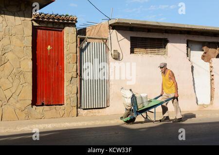 Man pushes wheelbarrow, Trinidad,  Cuba - Stock Photo
