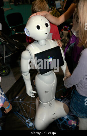 Children interacting with Pepper, a humanoid social robot,  in the Robot Zone at New Scientist Live 2017 - Stock Photo