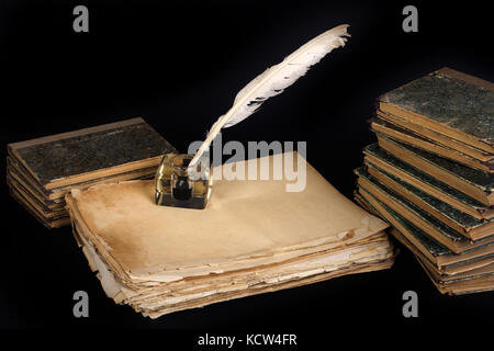 Vintage background with old ink bottle, books, papers and quill - Stock Photo