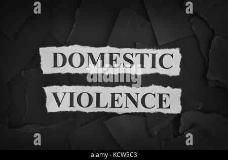 Torn pieces of black paper and words Domestic Violence. Concept Image. Black and White. Closeup. - Stock Photo