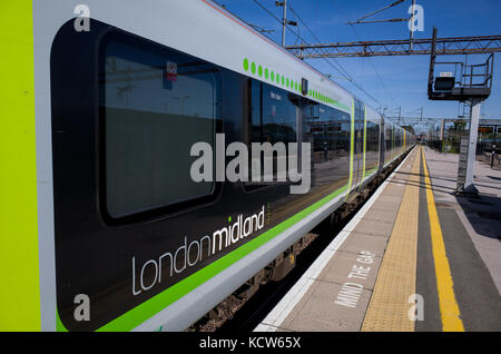 A London Midland train waits at the platform of Northampton Railway Station. - Stock Photo
