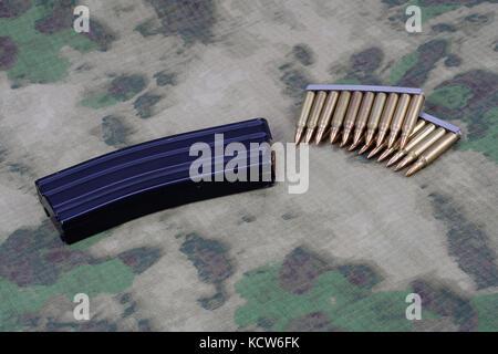 Ammunition with magazine on camoflage background - Stock Photo