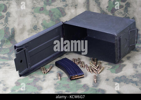Ammo Can with ammo on camoflage background - Stock Photo