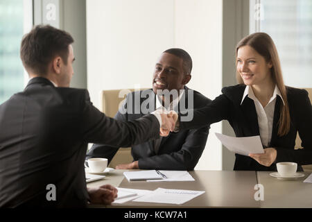 Smiling businesswoman handshaking with partner at beginning of multinational negotiations. Afro american entrepreneur - Stock Photo