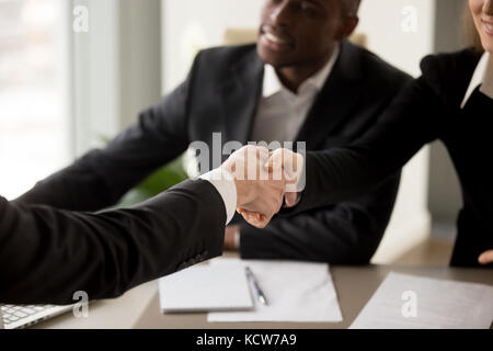 Close up image of business handshake between caucasian businesswoman and client or partner on multinational meeting - Stock Photo