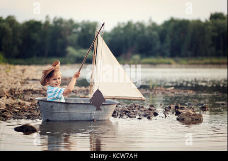 Little cute sailor on the river in the boat fishing, sailing - Stock Photo