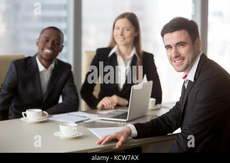 Portrait of friendly caucasian businessman sitting at negotiation table with multinational colleagues or partners - Stock Photo