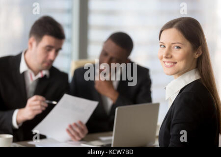 Portrait of pretty young woman in formal suit sitting on meeting, business negotiation or interview with african - Stock Photo
