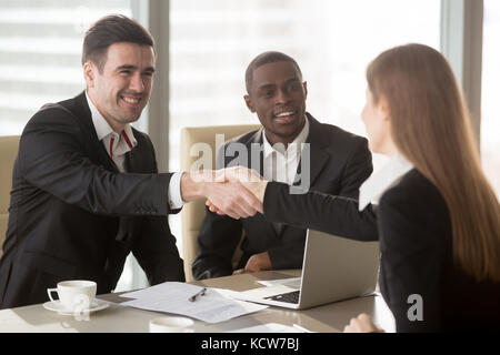 Happy smiling caucasian and afro american businessmen handshaking with female job applicant or businesswoman on - Stock Photo