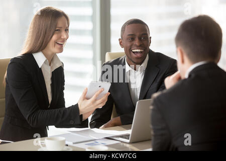 Happy smiling caucasian businesswoman using digital tablet at negotiations with multinational partners, laughing - Stock Photo