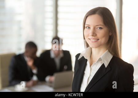 Portrait of beautiful millennial businesswoman looking at camera, multinational businessmen using laptop on background. - Stock Photo