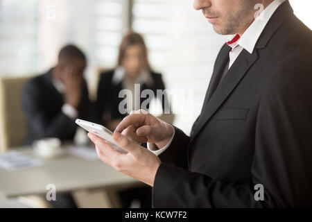 Close up image of businessman tapping on cellphone screen with finger, dialing number, writing message, man and - Stock Photo