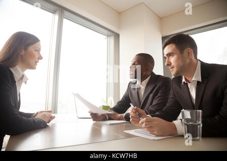 Multinational hiring managers conducting interview with caucasian young woman in formal wear. Millennial female - Stock Photo