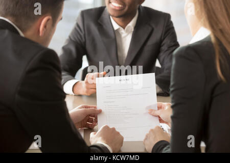 HR managers analyzing resume, asking afro american applicant about skills, actual work experience. Recruitment agency - Stock Photo
