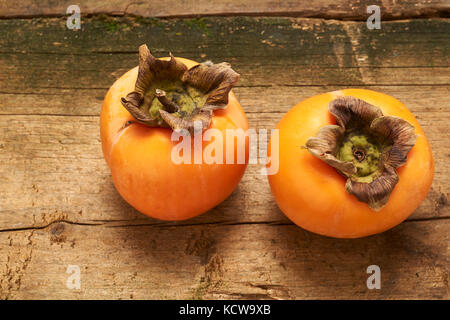 two delicious orange persimmon on an old wooden table - Stock Photo