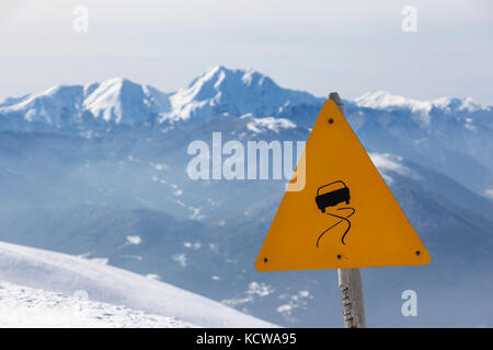 Slippery road sign, in winter landscape and mountains of snow. - Stock Photo