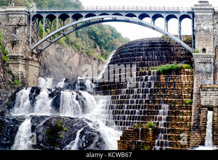 An old dam that stops the lake from flooding over is created by both natural and man made means with a bridge to - Stock Photo