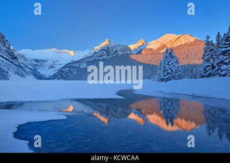 The Canadian Rocky Mountains reflected in Lake Louise at sunrise, Banff National Park, Alberta, Canada - Stock Photo