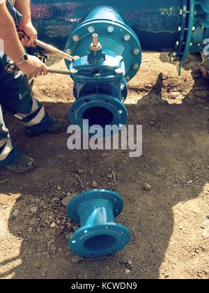 Worker hands with tools screwing  nuts on new dring water piping.   Piping with new Gate valves and reduction member. - Stock Photo