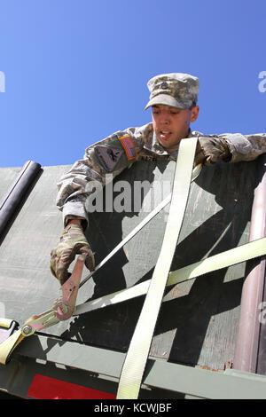 U.S. Army Staff Sgt. James Hazel, 1055th Transportation Company team leader, tightens a strap across a load of sandbags - Stock Photo