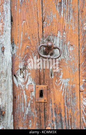 Detail of a old and distressed wooden door planks, with weathered brown paint and a bronze handle with a keyhole. - Stock Photo