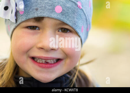 Portrait of pretty smiling little girl with one fallen out milk tooth - Stock Photo