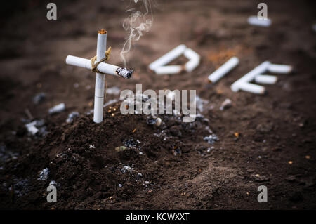 a cross from butts. Smoking kills. word die laid out the cigarettes on the ground next to the grave. the concept - Stock Photo
