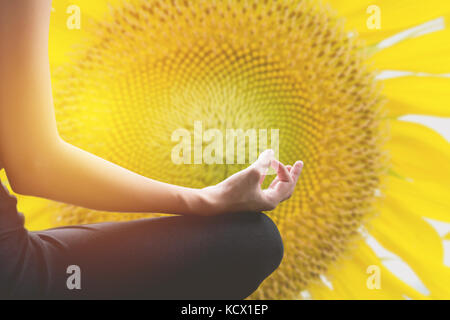 Close-up of feminine and masculine arms and crossed legs during meditation with nature background. - Stock Photo