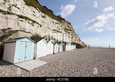Beach huts on shingle beach below white cliff, Beer, Devon, England, United Kingdom, Europe - Stock Photo
