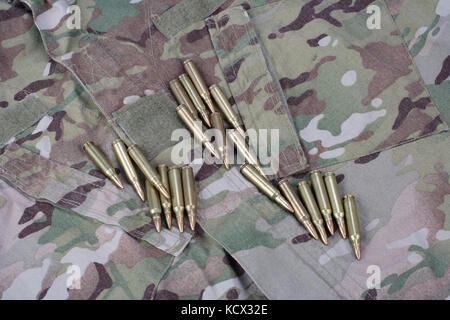 Ammunition on camoflage background - Stock Photo