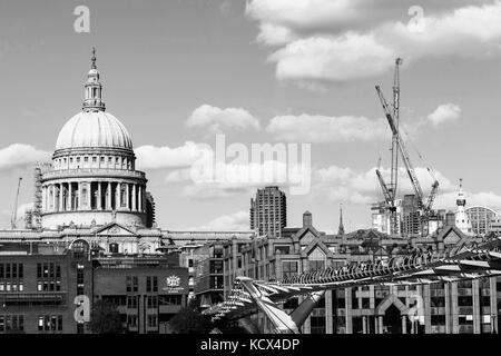 Black and White Monochrome Image of St Pauls Cathedral and the Millennium Footbridge Crossing the River Thames With - Stock Photo