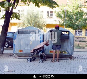 POGRADECI, ALBANIA, AUGUST 17 , 2014- A homeless man looking for food in a garbage dumpster. Urban Poverty - Stock Photo