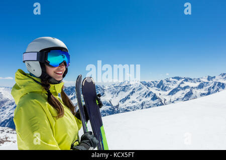 Happy young woman skier enjoying sunny weather in Alps. Winter sport and recreation, leasure outdoor activities. - Stock Photo