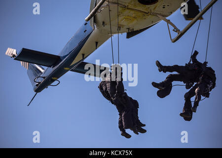 Special forces team helicopter rope jump, unmarked and unrecognizable swat team - Stock Photo