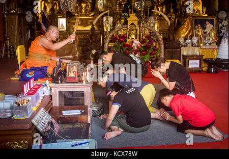 Monk blessing a family, in Wat Phra That Doi Suthep Temple of Chiang Mai, Thailand - Stock Photo