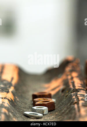 old rusty metal nuts on an old roof tile,shallow dof, - Stock Photo