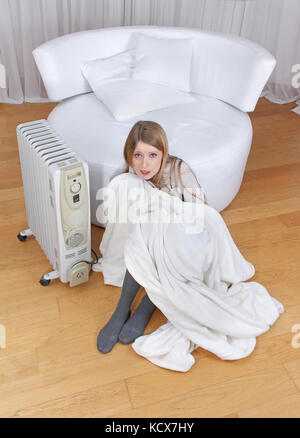 Young girl sitting on floor next to radiator feeling cold - Stock Photo