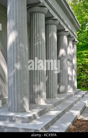 Roman or Greek inspired columns decorate the front of a building in a park - Stock Photo