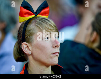 German woman wearing a bow with the German flag - Stock Photo