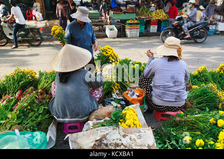 Flower vendors at the Hoi An market in Hoi An Ancient Town, Quang Nam, Vietnam. Hoi An is recognized as a World - Stock Photo