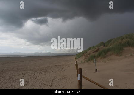 View along Harlech beach in dramatic weather, as storm hits. - Stock Photo